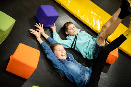 Cute twin brother and sister jumping and bouncing on indoor trampoline together when spending time in children play center. Sports and entertainment concept. Children's sports and hobbies.