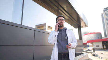 MS doctor in white coat talking on mobile phone front of clinic. Man medic outside speaking on cell phone. Medicine healthcare professional theme. Physician discussing with patient during phone talk.