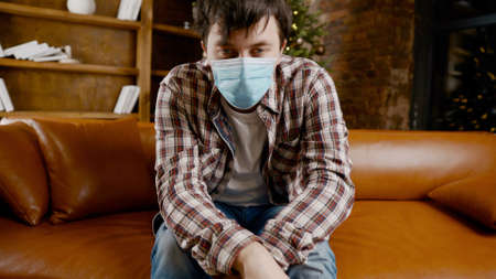 Unpleasant mood for Christmas holidays. Sad unhappy handsome man sits on the sofa wearing a mask. Feeling of hopelessness lockdown, quarantine virus.