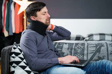 Tired strained man suffering from neck pain while working at computer. Male touchingly massages neck, puts on neck collar, sitting on couch, suffering from discomfort, long hours of sedentary overwork