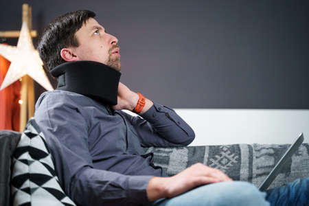 Business man overtime work massaging his neck while suffering from pain, uses a neck collar to relieve muscle tension. Man with health problems suffered neck injury naccident, dullness due overwork.