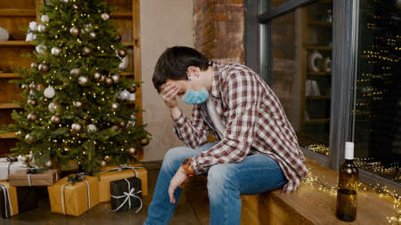 Problems of alcoholism in loneliness, sadness and melancholy during pandemic  Male removes mask from virus, drinking wine from bottle during new year holidays sitting by Christmas tree