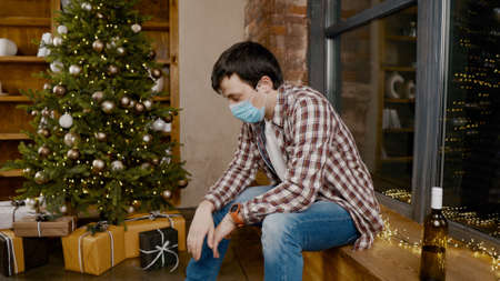 Lonely man wearing face mask very upset and drunk, sitting by window and Christmas tree and drinking alcohol from bottle. Topic alcohol addiction, depression during quarantine virus Reklamní fotografie