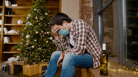 Lonely man wearing  face mask very upset and drunk, sitting by window and Christmas tree and drinking alcohol from bottle. Topic alcohol addiction, depression during quarantine