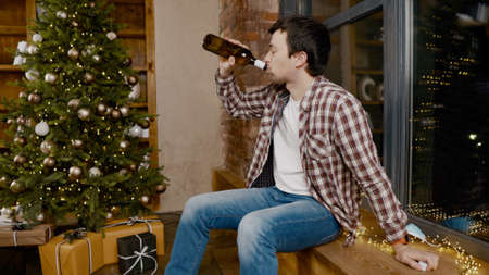 Problems of alcoholism in loneliness, sadness and melancholy during pandemic virus Male removes mask from virus, drinking wine from bottle during new year holidays sitting by Christmas tree