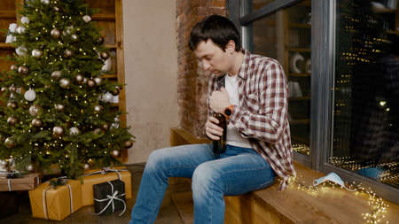 Lonely man wearing  face mask very upset and drunk, sitting by window and Christmas tree and drinking alcohol from bottle. Topic alcohol addiction, depression during quarantine virus