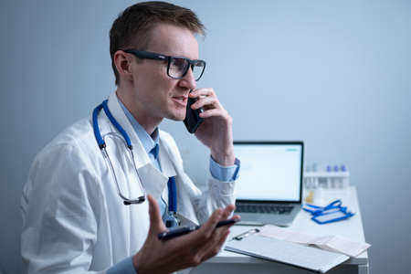 Smiling doctor having phone call at desk. Physicianr talking with his patient in office clinic sitting at table with laptop. German doctor in white lab coat works hospital, consults online by phone