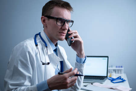European doctor in white medical coat and glasses consults patient on cell phone in clinic office, sitting at table with laptop. German general practitioner at workplace in hospital talking on phone