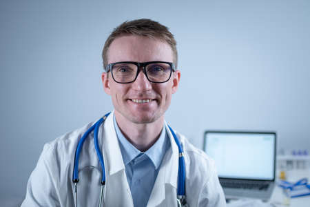 Portrait of adult handsome family doctor in medical office. Successful physician in white lab coat looking at camera and smiling in hospital clinic. Young general practitioner wear glasses smiling.