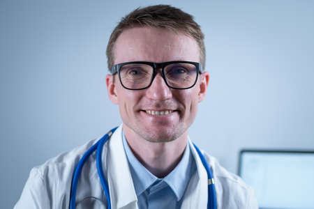 Happy confident male professional medic doctor close up portrait. Smiling doctor wear uniform looking at camera in office. Close-up of handsome German smile general practitioner wearing glasses Reklamní fotografie