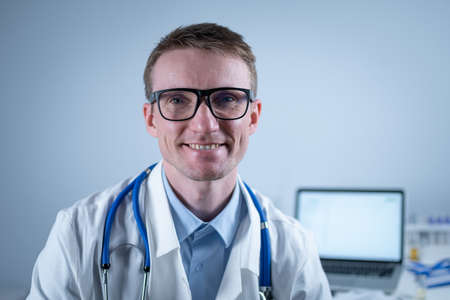 Portrait of adult handsome family doctor in medical office. Successful physician in white lab coat looking at camera and smiling in hospital clinic. Young general practitioner wearing glasses smiling