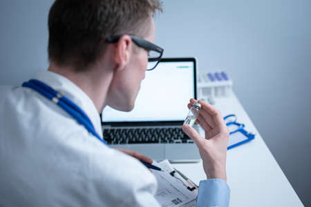 Concept of medicine and immunization of human body against infections, viruses to prevent epidemics of diseases. Scientist examines vial of medicine and works on laptop in medical laboratory. Vaccine Фото со стока