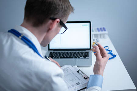 Scientist in medical laboratory examines vial of medicine, vaccine against viruses, influenza, covid. Doctor enters information into computer about investigation. Immunization from terrible diseases Фото со стока
