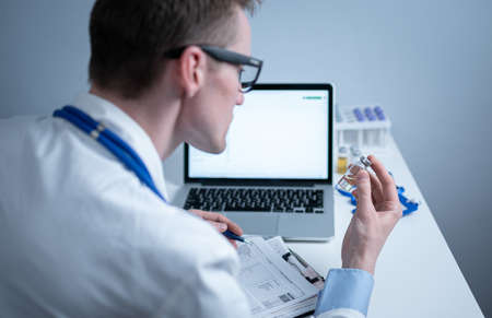 Young caucasian doctor working at table in hospital laboratory examining an ampoule of medicine and entering data into computer. New vaccine against coronavirus. Scientist changing future covid 19