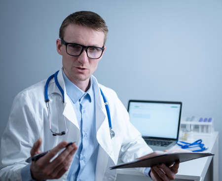 Young male doctor consults patient in hospital office, holding medical examinations in hands. General practitioner in white medical coat looks into camera and makes an appointment with patient online Фото со стока