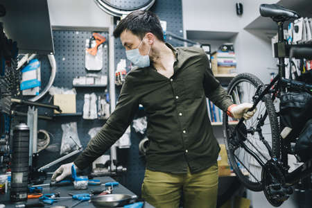Bicycle shop repairman works in bicycle service and repair workshop during coronavirus quarantine wearing face shield and gloves, new norm. Mechanic repairing bicycle wheel wearing medical mask Фото со стока