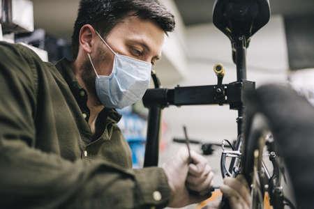 Mechanic repairs bicycle in workshop wearing covid 19 mask. Worker of bicycle store fixes bike during coronavirus quarantine in protective mask. Repairman maintenance cycle. Sport shop concept