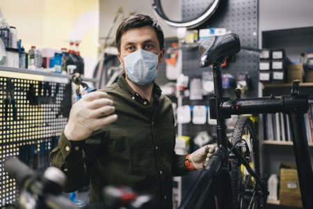 Bicycle mechanic wearing protective mask and gloves repairs customers bicycle wheel in accordance with quarantine standards during coronavirus pandemic. Small business during covid 19 lockdown