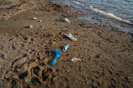 Ocean pollution. consequences overuse of surgical masks during  pandemic. Dirty used  medical mask on beach washed by sea wave. Pollution with medical waste.