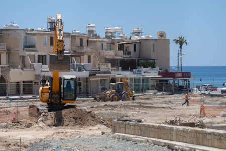 May 11, 2021 Cyprus, Paphos. Construction machinery during road repair work at construction site near harbor in Paphos city. Road construction works. Construction site against buildings in downtown