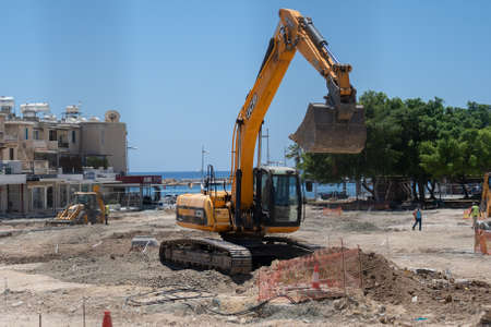 May 11, 2021 Cyprus, Paphos. Heavy machinery and construction equipment are working on renovation of pavement near harbor in downtown Paphos. Road repair concept. Backhoe loader on construction site