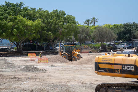 May 11, 2021 Cyprus, Paphos. Construction work with construction equipment and road renovation workers in city near harbor. Road construction works with excavator, bulldozer and truck near houses