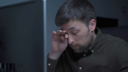 Tired male working on computer. Sad exhausted man at home office. Stressful work, stress at workplace. Software developer looks very tired during completion overtime of project, working on computer Standard-Bild