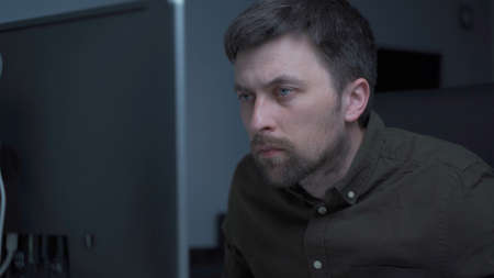 Young caucasian man working overtime at computer and eye fatigue from monitor in home office. Male having stressful time working on PC. Exhausted programmer stressful work, stress at workplace Standard-Bild