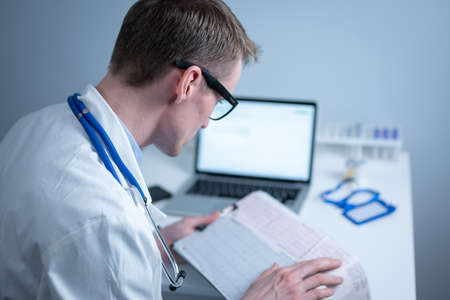 Young handsome doctor man in glasses and white lab coat examines results of electrocardiographic examination of patient heart in hospital office. Cardiologist looking at cardiogram at medical office