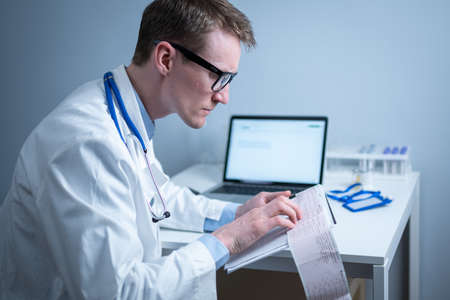Cardiologist reading an ECG print-out. Doctor analyzing electrocardiogram. Practitioner examine patient test results. Medical and healthcare concept. Physician looking at cardiogram at medical office