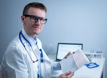 Topic of timely checking for heart disease. Heart disease myocardial infarction. Doctor analyzing electrocardiogram at the desk in hospital office. Cardiologist at work in clinic. doctor look at EKG Stock Photo