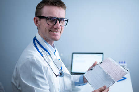 Topic of timely checking for heart disease. Heart disease myocardial infarction. Doctor analyzing electrocardiogram at the desk in hospital office. Cardiologist at work in clinic. doctor look at EKG