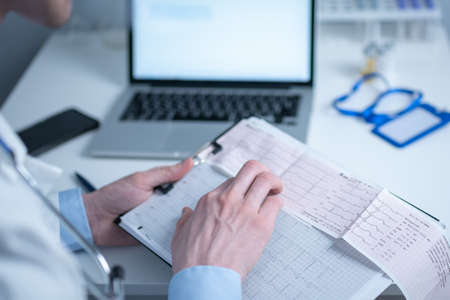 Cardiologist reading an ECG print-out. Doctor analyzing electrocardiogram. Practitioner examine patient test results. Medical and healthcare concept. Physician looking at cardiogram at medical office Standard-Bild