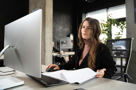 Design and architecture theme. A female young architect is working on a project with blueprints at the computer in a modern office. Architect engineer woman working plan at counting room