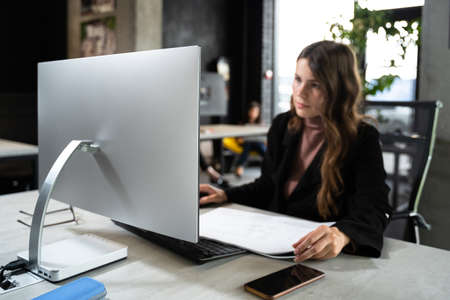 Female designer in office working on architects project. Business woman, view architectural drawings in office behind desk. Architect engineer works with technical drawings. Creator worke in studio Standard-Bild