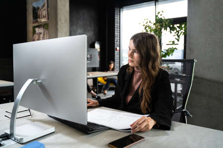 Young woman architect working with blueprints and technical design project at work table and computer in office. Designer using architectural plans of buildings, working at computer, creates project Standard-Bild
