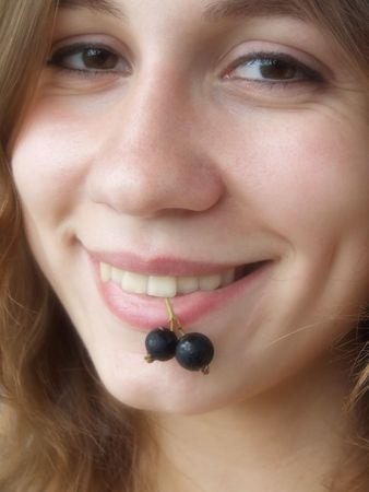 Smiling girl with berries in her teeth photo