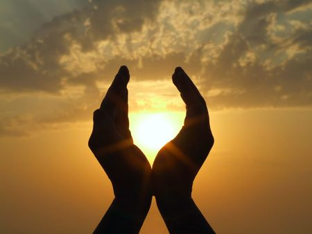 hands praying: hands holding the sun at dawn
