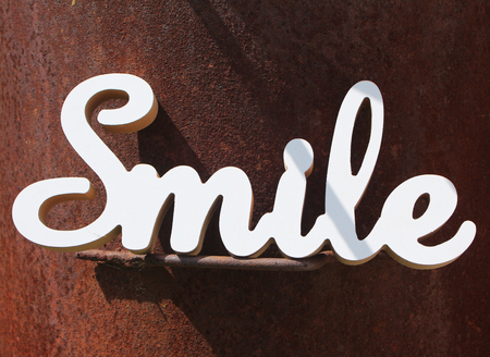 positive smile text on rusty iron background
