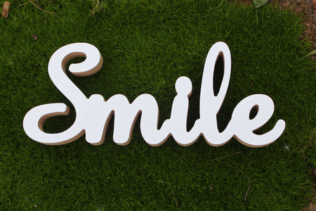 3d white text smile on green grass background