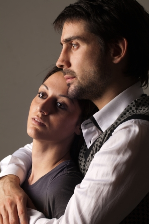 confidentially: young couple in the studio on a black background