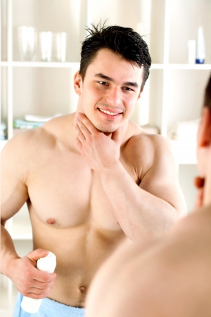 body grooming: athleteyoung guy shaves in the bathroom