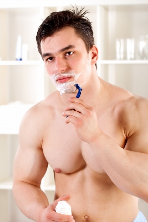 athlete is a young guy shaves in the bathroom photo