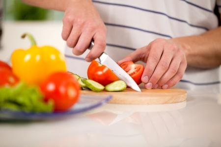 man chops vegetables for a salad