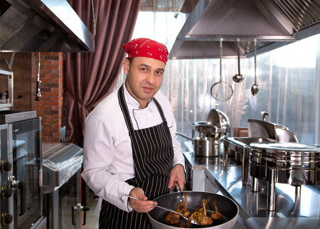 hotel staff: chef in the kitchen at the restaurant for cooking corporate cuisine