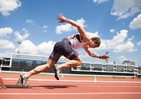 giovane atleta muscolare è all'inizio del treadmill allo stadio Archivio Fotografico