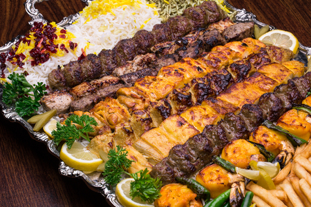Close up of Persian Mix Kebab consist of minced meat chicken and steak with rice in large tray