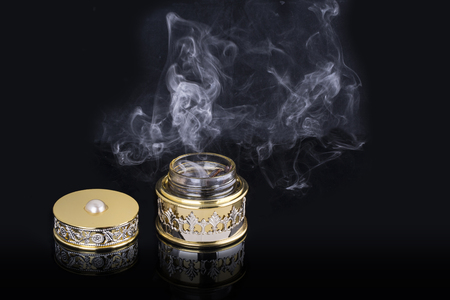 Incense of Traditional Arabian Fragrance Oudh Bakhoor in a maroon glass jar on light background