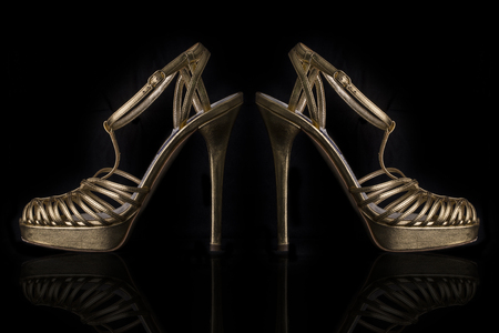 A Pair of Gold Leather High Heels Sandals on Black  Background