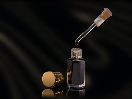 Wierook van traditionele Arabische geur olie in een glazen pot en dropper neerzetten op zwarte achtergrond Stockfoto